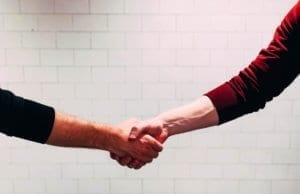 two men shaking hands with a white brick background