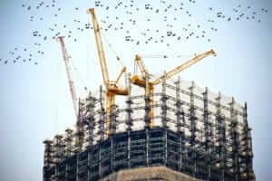 cranes on a large building under construction