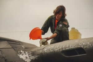 a pilot using a funnel to put liquid into an old airplane