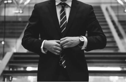 man buttoning a business suit wearing a striped tie