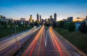 long exposure photo of headlights on a city highway at sundown