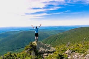 man celebrating with his hands in the air standing on top of a mountain