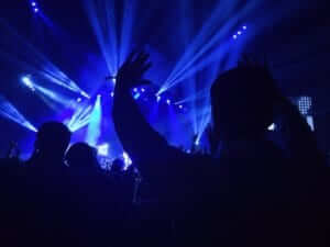 a person with their hands up at a concert