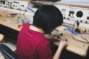 a person working on circuitry with a soldering and other components on a table