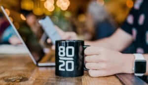 "a person working on a laptop holding a mug with ""80/20"" printed on it"