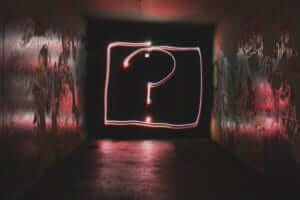 a question mark made with light at the end of a graffiti painted hall