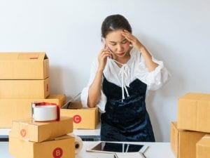 Woman frsutrated with packing boxes for her business