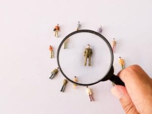 Photo of magnifying glass and tiny toy people against white background