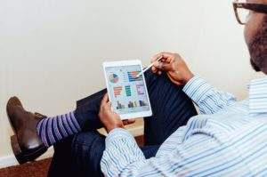 A man looking at charts on an iPad