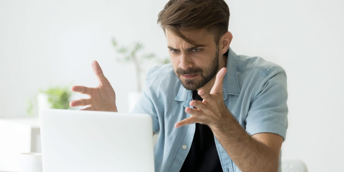 a photo of man looking frustrated while working on a laptop